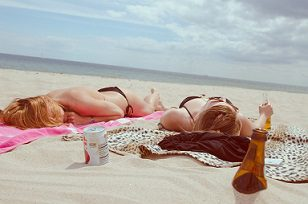two girls laying on beach drinking