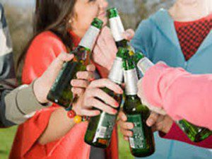 teens clinking beer bottles together