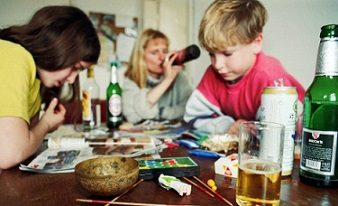 two kids at table around alcohol