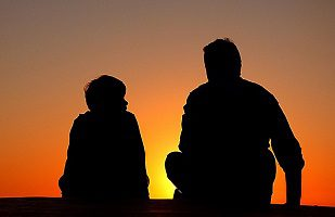 father and son watching sunset