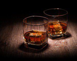 shutterstock - glasses of whiskey on wooden table