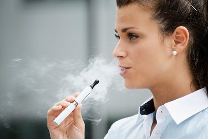 young woman smoking electronic cigarette outside office building
