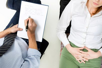 counseling - male psychiatrist writing notes with female patient lying back