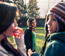 isolated female teen in background with two other talking blurry in foreground