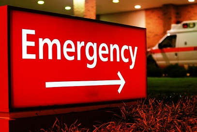 red Emergency sign with arrow in foreground and ambulance in background