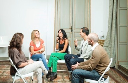 group of people sitting in circle and talking