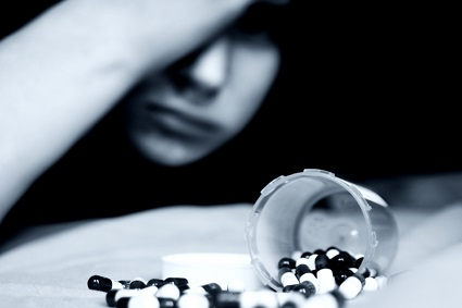 Teen with pills - black and white photo with spilled bottle of pills in foreground and teen blurred in background