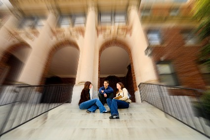 College campus 2014 - students sitting on steps in front of archway