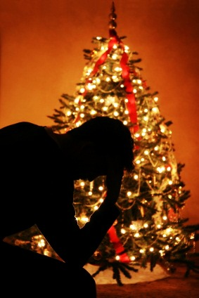 Navigating Holiday Stress 2014 - silhouette of person holding head in front of Christmas tree
