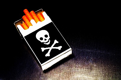 Smoking kills - open pack of cigarettes with skull and crossbones on box