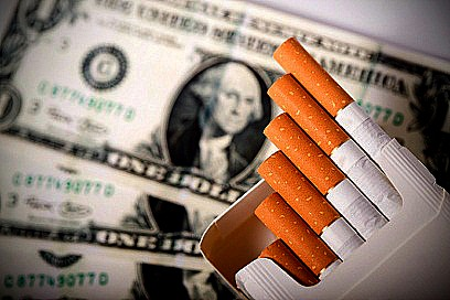 Smoking cost - pack of open cigarettes with dollar bills in background