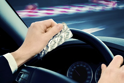 Driving and drugs - hands on steering wheel with empty pill packet