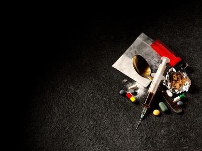 Rx to Heroin- pile of pills, spoon, heroin, syringe