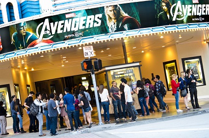 people standing in front of movie theater Avengers marquee