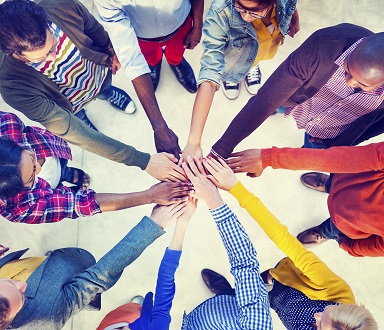 diverse group of people in circle extending hands to meet in center