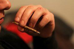 guy holding marijuana cigerette