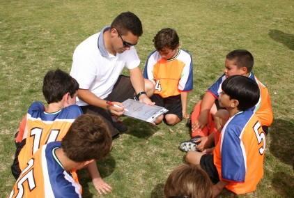 Game Plan - coach reviewing with boys team on field