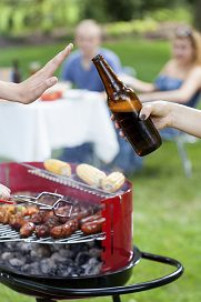 person grilling on barbecue declining offered beer