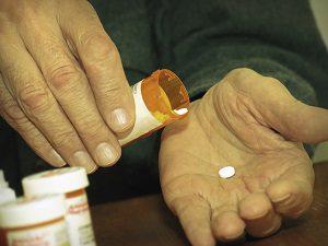 hand of senior with white pill prescription bottle